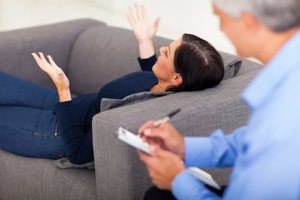Woman on couch undergoing cognitive behavioral therapy CBT