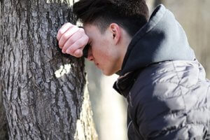 A man leans against a tree thinking about how he may need PTSD therapy and a PTSD psychiatrist.